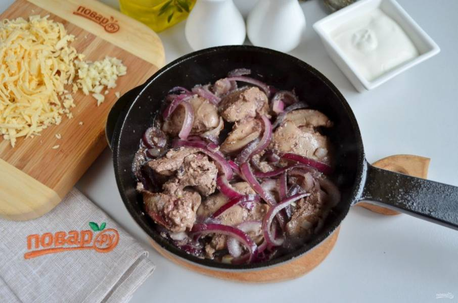К полуобжаренной печени добавьте красный лук, соль и жарьте до мягкости лука.