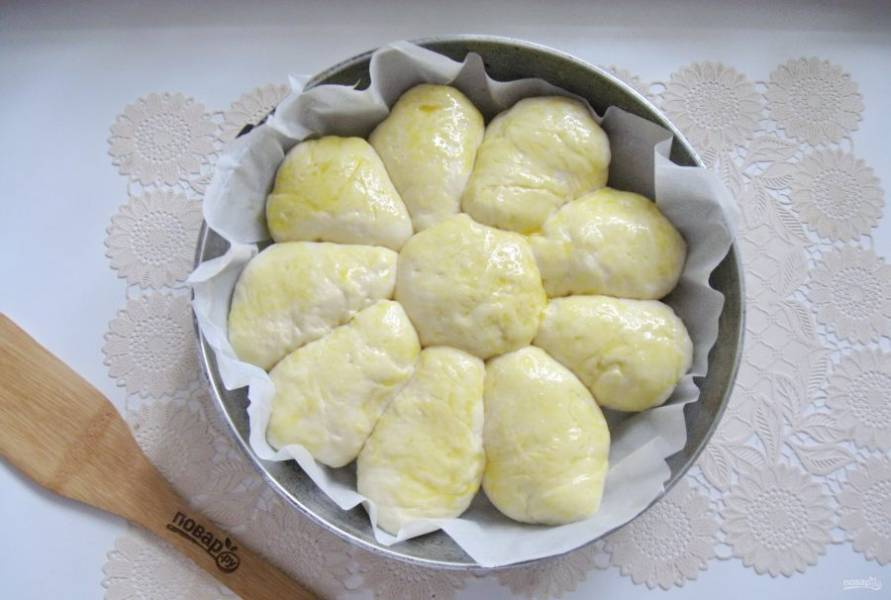 Выложите булочку посередине сковороды, а пирожки по краю. Дайте постоять пирогу в тепле 30-35 минут. Смажьте яйцом и отправьте в духовку, разогретую до 175 градусов.