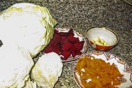 Капусту помыть, отделить ненужные листья, затем пошинковать на крупные кусочки. Морковь также помыть, очистить, и нарезать пластинками. Свеклу хорошенько помыть, очистить от кожуры и тонко нарезать. Чеснок очистить и нарезать дольками.
