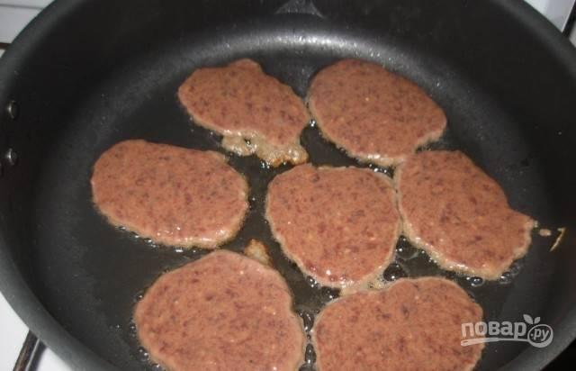 Разогрейте масло на сковороде. Влейте в него котлеты ложкой, используя половину фарша.