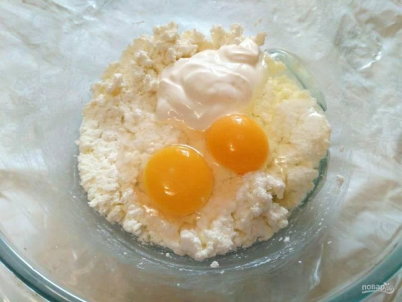 Добавьте в творог сметану и вбейте яйца, соедините ингредиенты в однородную массу.