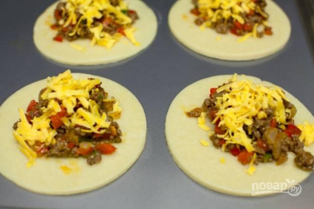 Достаньте тесто и раскатайте в пласт около 3 мм толщиной, вырежьте круги диаметром 10-12 см. На каждый положите по немного начинки и присыпьте тертым сыром.