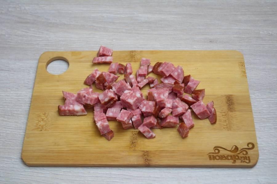 5. Варено-копченую колбасу нарезаем небольшими кубиками. Не забудьте удалить оболочку у колбасы. При варке она уплотнится и станет грубой, испортит вкусовые качества супа.