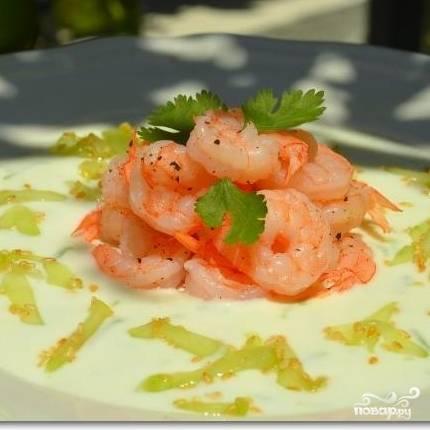 Красиво собираем салат: в центр тарелки выкладываем креветки, вокруг - соус, на соус - огурцы с семечками. Приятного аппетита! :)