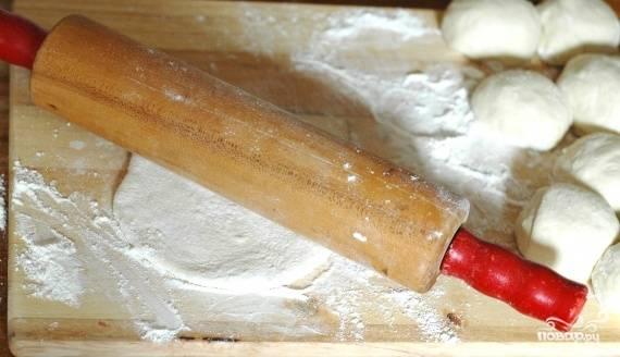 Формируем лепешки. Выкладываем тесто на рабочую поверхность, присыпанную мукой. Скатываем тесто в толстую колбаску, делим ее на несколько одинаковых частей. Каждый полученный кусочек теста раскатываем в тоненькую лепешку. В центр полученных лепешек выкладываем начинку. Пальцами поднимаем края лепешки. Соединяем их сверху, тем самым пряча начинку внутри теста. Раскатываем наше изделие еще раз, чтобы придать ему форму лепешки.