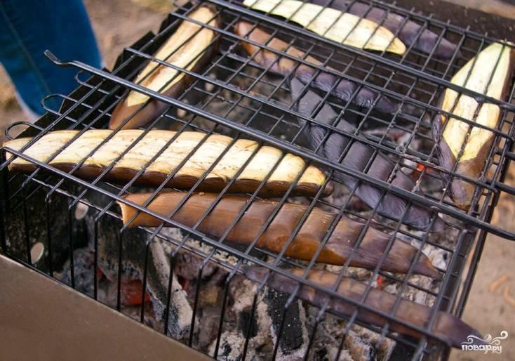 Грибы обжариваем с двух сторон (по 15 минут с каждой). Опять же: время приготовления зависит от жара углей и расстояния от решетки до них. Когда грибы зарумянятся и перестанут сильно выделять сок, снимаем их с костра. Теперь настала очередь запекать баклажаны. Я их разрезала вдоль, так они лучше держатся над костром. Кладу решетку опять на мангал. Обжариваю баклажаны с обеих сторон по 10 минут.