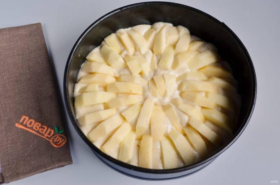 6. Форму застелите пергаментом (берите диаметр формы 20-22 см, не больше). Смажьте. Распределите ровно тесто. Яблоки вымойте, очистите от кожуры и сердцевинок, порежьте дольками. Вставьте дольки в тесто, чем больше яблочных долек, тем вкуснее пирог.