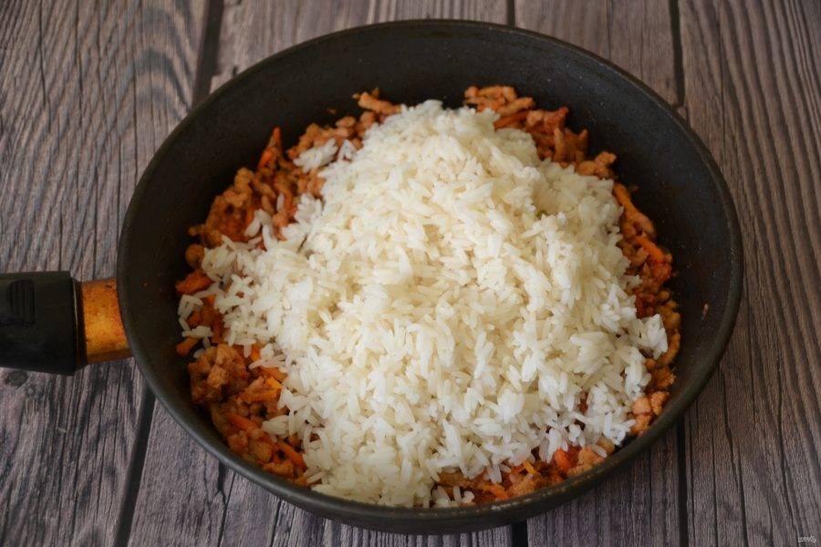 Выложите отварной рис к мясному фаршу, перемешайте и готовьте все вместе еще примерно 5 минут.