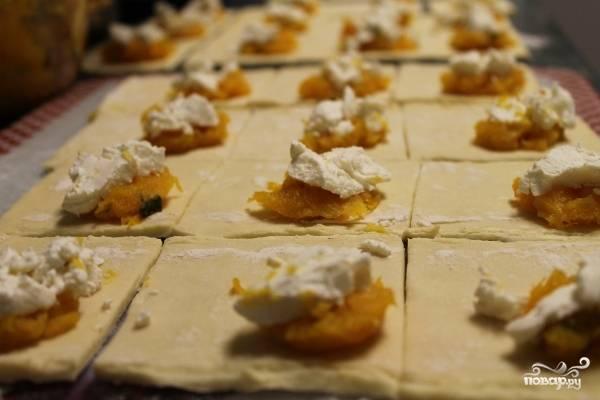 2. Теперь раскатаем тесто в пласт, нарезаем квадратиками. Выкладываем по центру каждого пюре из тыквы и немного сыра.