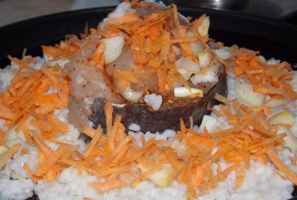 Пока рыба маринуется, до полуготовности отвариваю рис, натираю морковь. Затем блюдо для выпекания смазываю маслом, выкладываю рис (добавляю немного воды или сметаны), выкладываю рыбу, посыпаю все морковью.