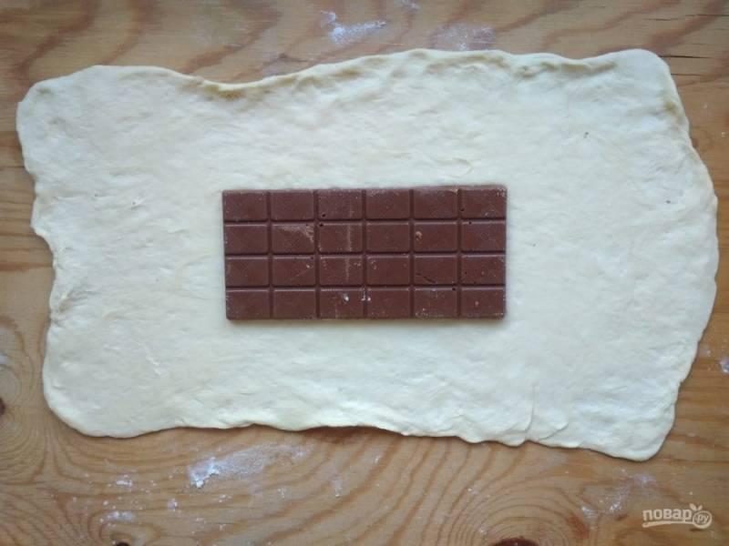 2. Раскатайте тесто в прямоугольник. В центр выложите шоколад.
