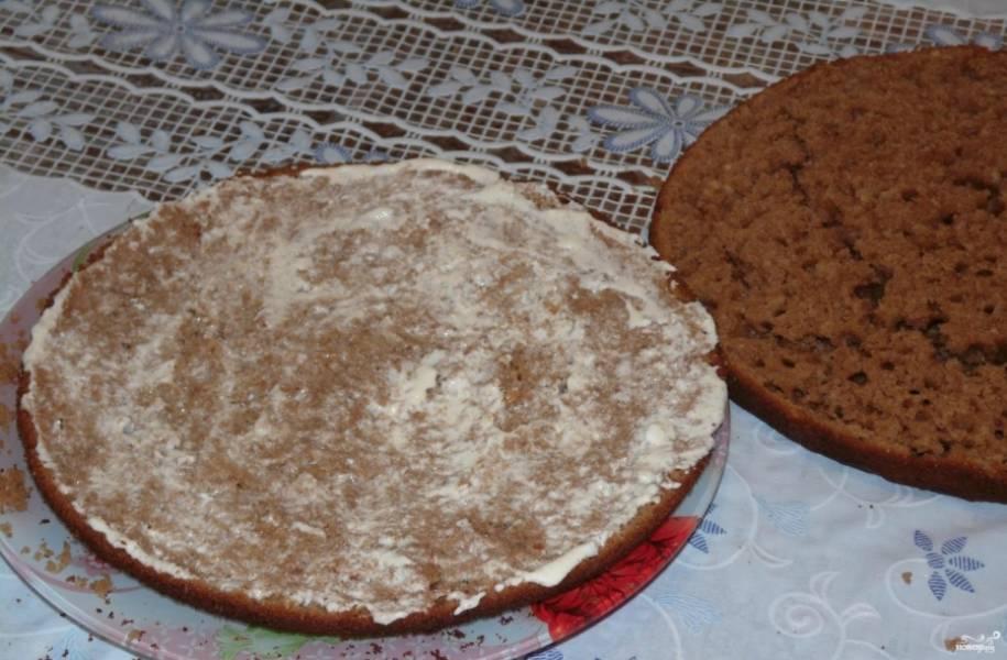 6.Готовый торт достаем из духовки, немного остужаем и вынимаем из формы. Разрезаем его на 2 коржа и перемазываем сметаной с сахаром.