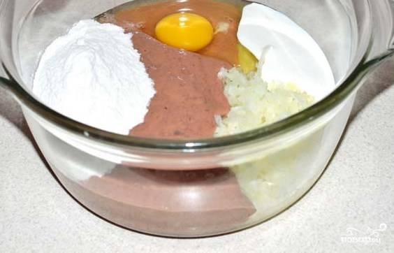 Добавьте к смеси сметану, яйцо, муку. Также всыпьте соль и приправу. Всё перемешайте, затем уберите в холодильник на 10 минут.
