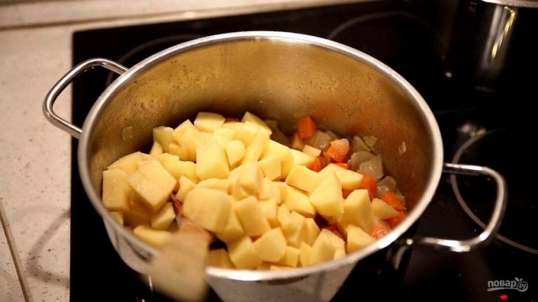 Когда овощи поджарятся, добавьте нарезанный картофель. Залейте овощным бульоном и варите до готовности.
