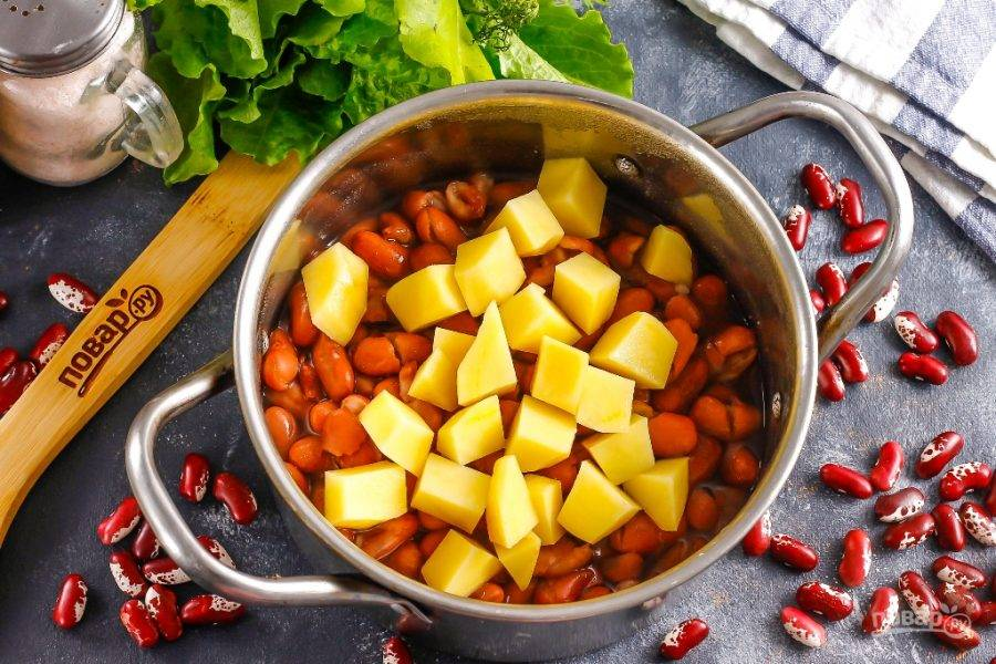 Картофель очистите от кожуры, промойте в воде и нарежьте средними кубиками. Всыпьте в емкость к фасоли, отварите еще 10 минут.
