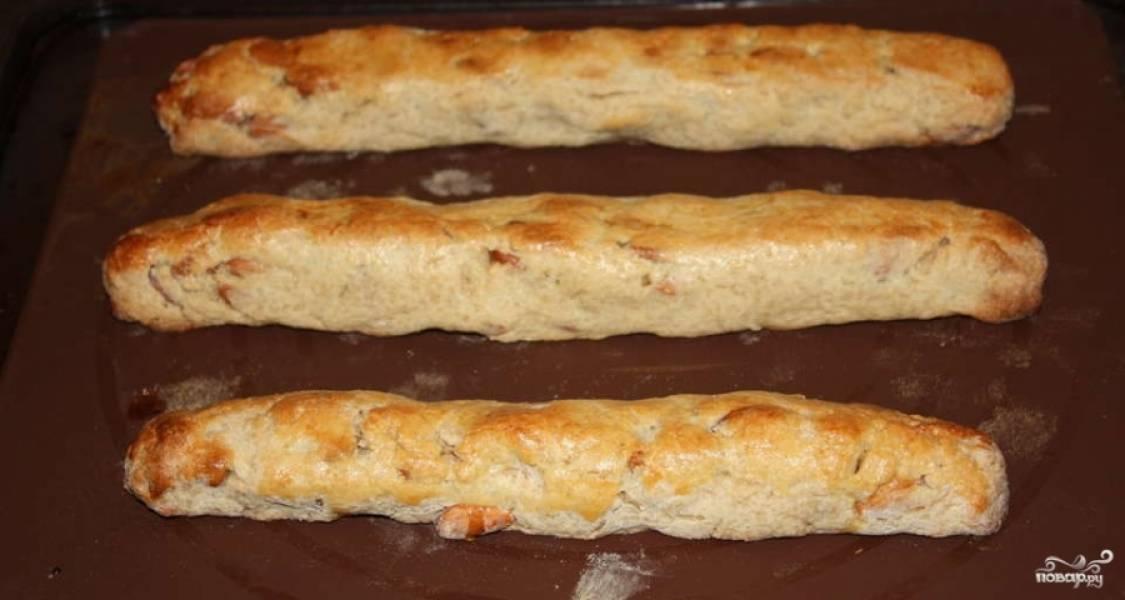 3.Готовое тесто разделяем на кусочки и из каждого раскатываем колбаски диаметром по 3-4 сантиметра. Выкладываем их на противень и смазываем взбитым яйцом. Отправляем в духовой шкаф на 20-25 минут при температуре 180 градусов.