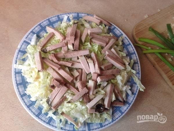 Можно все подготовленные ингредиенты сложить в миску и перемешать, а можно подать и вот так, каждому свою порцию. Выкладываем на тарелку часть пекинской капусты, поверх нее — мясо.