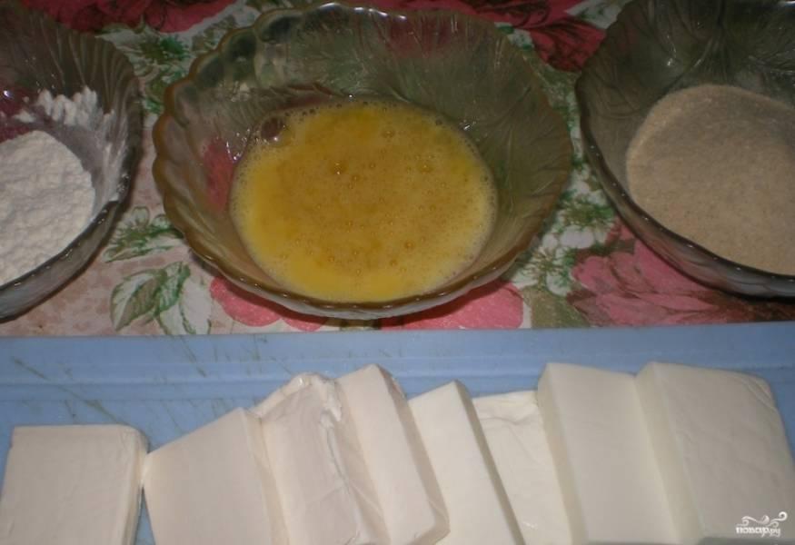 Каждый сырок разрежьте на 4 части. Яйцо в мисочке взбейте со специями и солью.