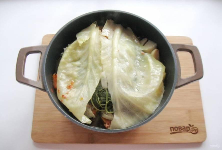 Доведите мясо с овощами до кипения на среднем огне. Проварите 15 минут. После убавьте огонь до минимума. Басма должна буквально томиться в течение 1,2-1,5 часов. Из готового блюда удалите листья капусты и зелень.