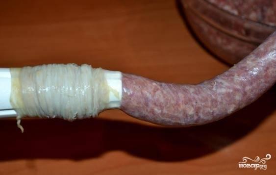 5. Наденьте тщательно помытую кишку на приспособление для колбасы. Перед этим смажьте его постным маслом. Возьмите немного фарша, заложите его в мясорубку. Не спеша набивайте оболочку. Как можно чаще формируйте «звенья» колбаски.