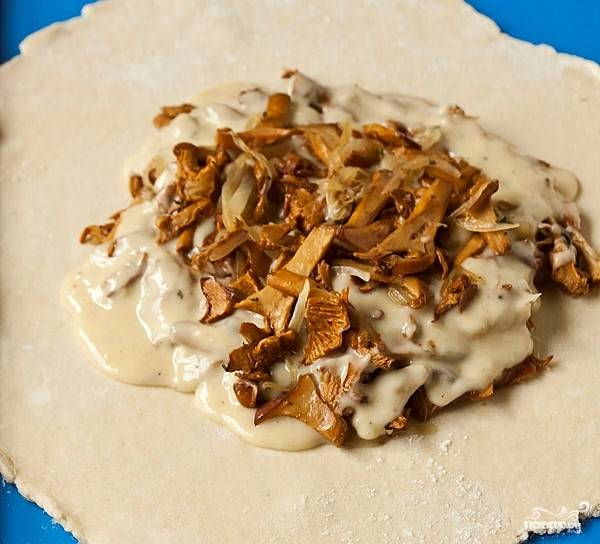 Тесто достаем из холодильника, делим на несколько частей и раскатываем лепешки. В центр укладываем начинку и соус.