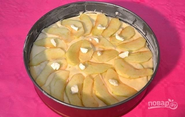 Сверху покройте пирог ломтиками яблок и добавьте небольшие кусочки сливочного масла. Выпекайте пирог в предварительно разогретой духовке в течение 40-50 минут при температуре 180 градусов.