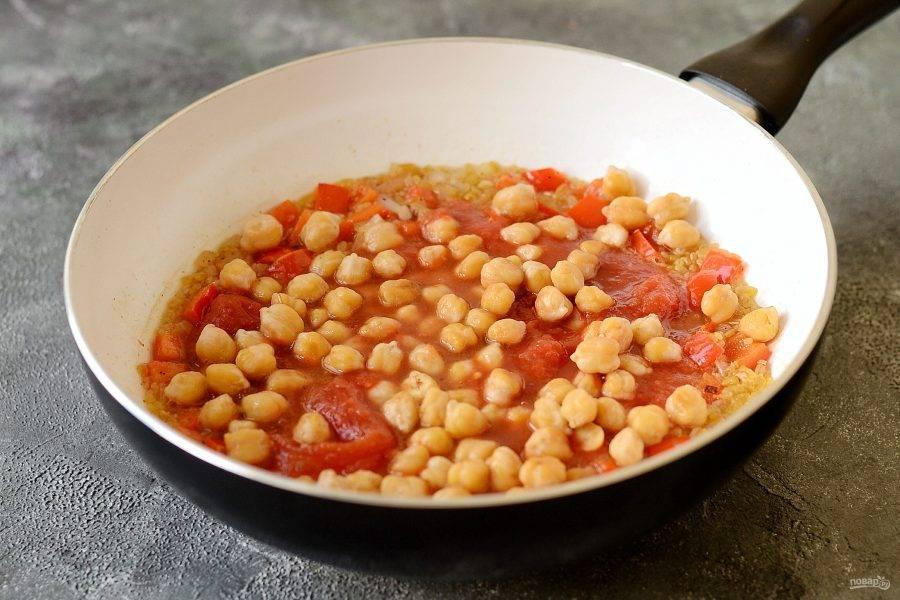 Влейте бульон, добавьте нут и рубленые томаты. Доведите до кипения. Накройте крышкой, и  варите на медленном огне 15 минут. Жидкость должна полностью впитаться.
