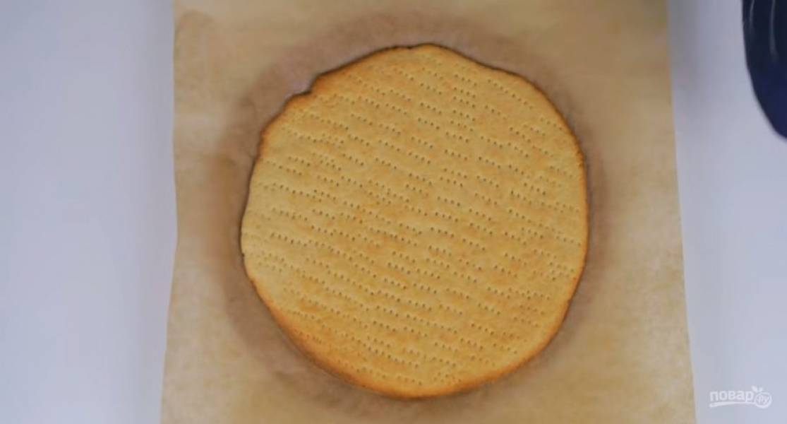 3. На посыпанной мукой бумаге с силиконовым покрытием раскатайте одну часть теста в пласт размером чуть больше дна разъемной формы для выпечки. Наколите тесто вилкой и выпекайте в разогретой до 180 градусов духовке 15-17 минут.