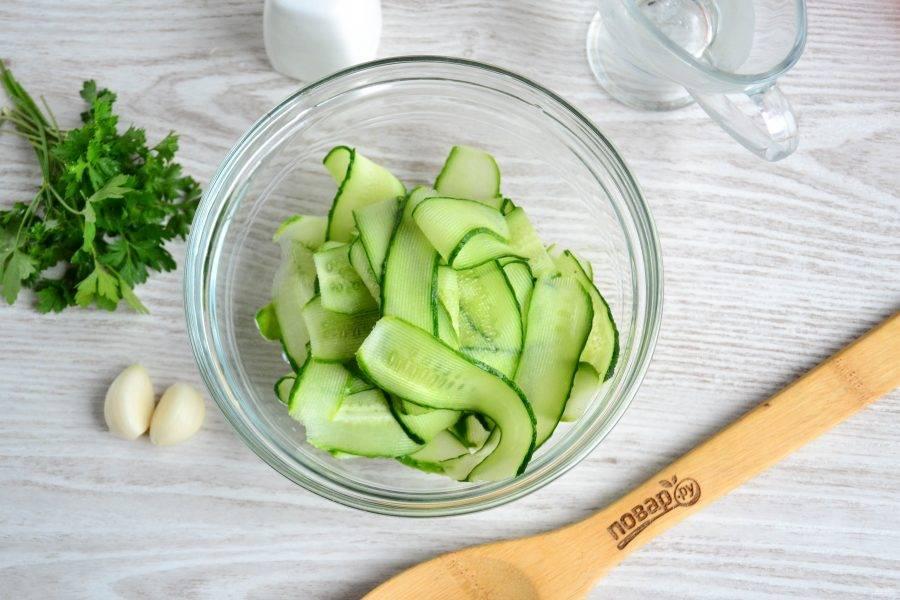 Огурцы хорошо помойте и нарежьте овощечисткой на тонкие слайсы.