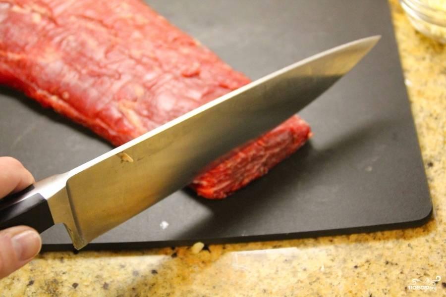 Подготовьте говяжью вырезку. Помойте и нарежьте её тонкими кусочками.