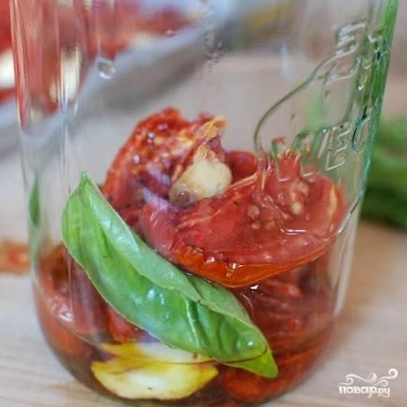 Наполняем баночку сушеными помидорами, чесноком, свежим базиликом.