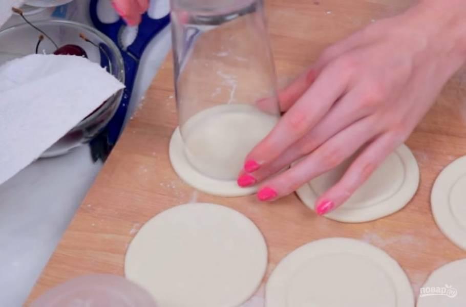 1. Слоеное тесто извлеките из упаковки и слегка раскатайте скалкой. Затем вырежьте круги стаканом, это будут наши пирожки. На каждом круге с помощью стакана чуть поменьше диаметром выдавите еще один круг.