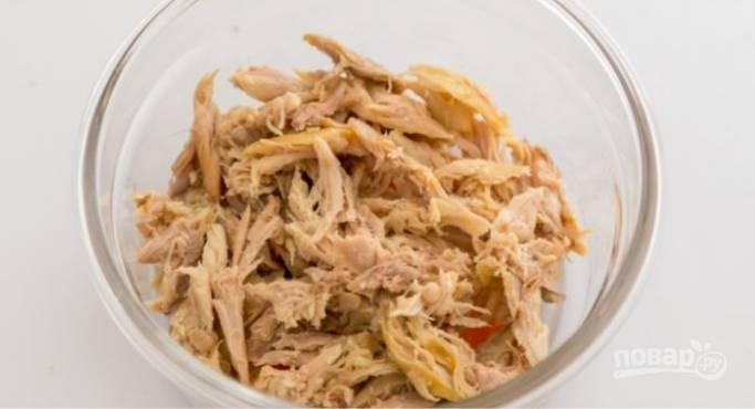 7.Поверх моркови выложите немного куриного мяса, что разобрали на тонкие волокна, залейте мясо бульоном.