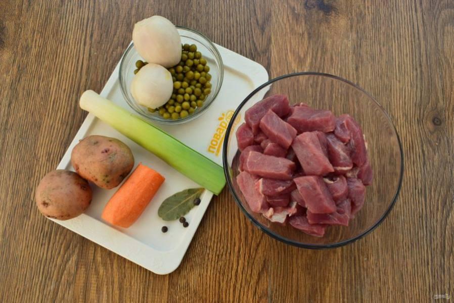 Подготовьте необходимые продукты. Мясо промойте, обсушите, нарежьте на кубики по 2 см. Овощи помойте. Морковь и лук очистите.