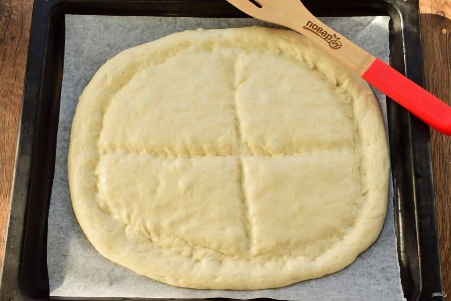 Тыльной стороной ладони или рукоятью ножа сделайте углубления по краю и крестом по центру лепешки. Отправьте матнакаш в разогретую до 200 °C духовку на 15 минут до золотистой корочки.