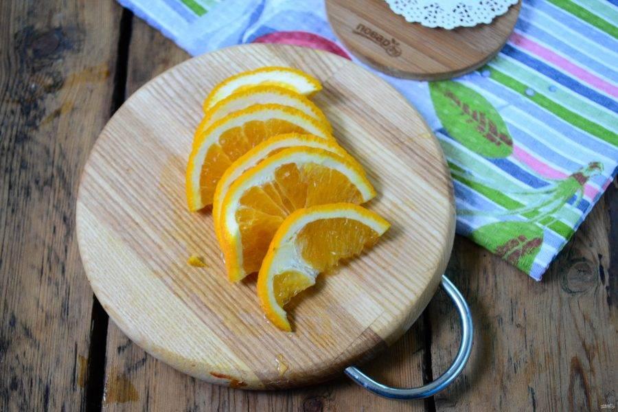 Апельсин порежьте на дольки. Обратите внимание: можно использовать только мякоть апельсина, а можно брать и цедру. Я не очищаю апельсин, его цедра придает компоту насыщенный вкус.