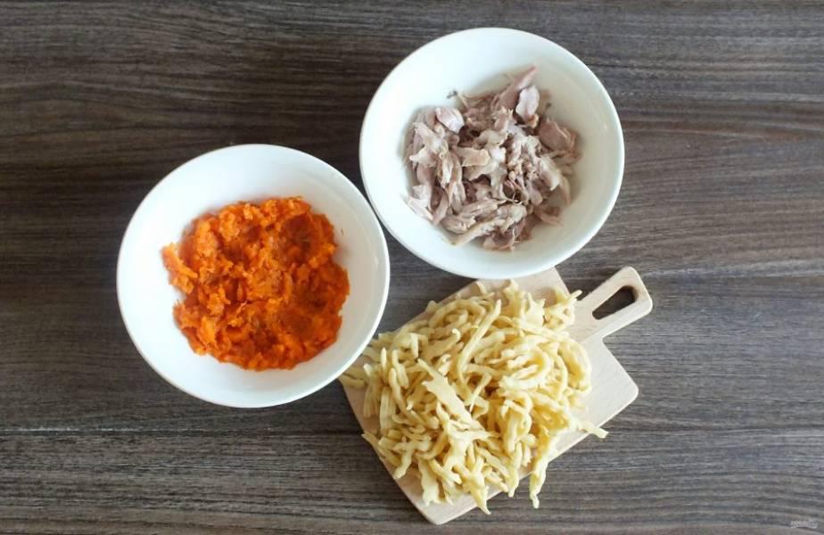 Отварную морковь натрите на мелкой тёрке или разомните вилкой. С супового набора снимите мясо, нарежьте помельче. Подготовьте лапшу.