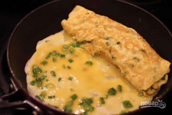 5.Заметили, что яйцо прихватилось, сверните его рулетом вместе с тем рулетом, что уже на краю сковороды. Повторите все действия, пока есть яичная смесь (3-4 слоя).