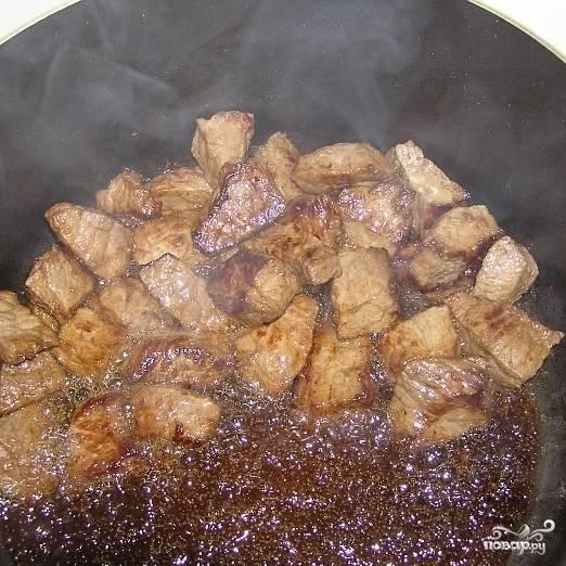 Параллельно этому разогреваем в другой посуде еще немного масла и обжариваем в нем кусочки говядины размером примерно 3 на 3 см. Обжариваем на очень быстром огне - нам нужно, чтобы мясо покрылось корочкой. Чтобы мясо именно жарилось, а не тушилось в собственном соку, обжаривать нужно небольшими партиями - у меня было 3 захода.