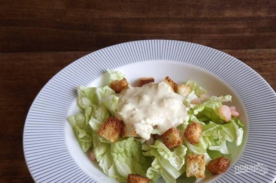 Заправьте салат соусом, разложите его по тарелкам. Украсьте креветками, тертым пармезаном и оставшимися хлебными гренками.