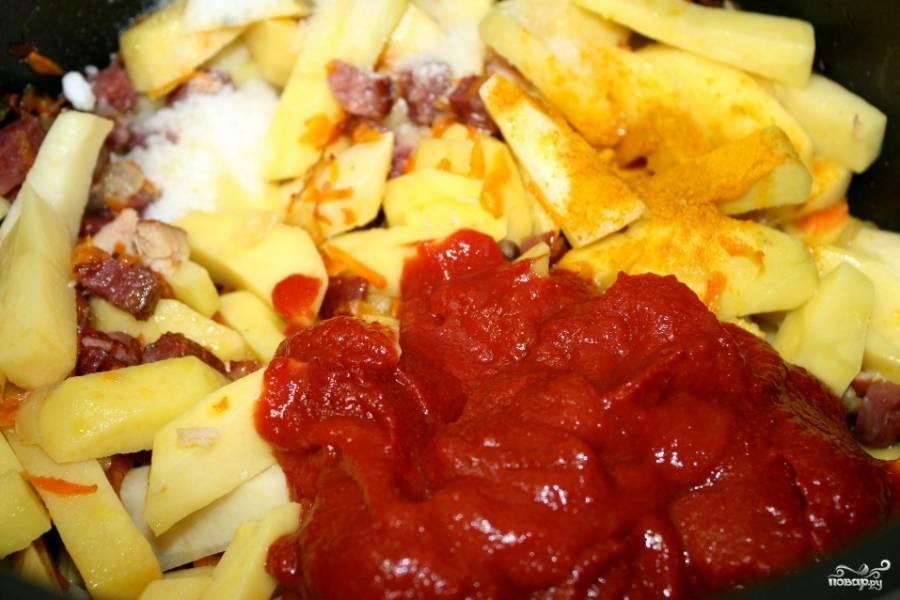 Переложите обжаренные продукты в большую кастрюлю, добавьте томатную пасту, специи, шафран или куркуму. Залейте все водой или бульоном. Варите на среднем огне час-полтора. Солянка скорее даже тушится, чем варится.