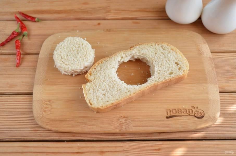 С помощью стакана вырежьте серединку в кусочке хлеба. Если яйца крупные, то можно чуть больше.