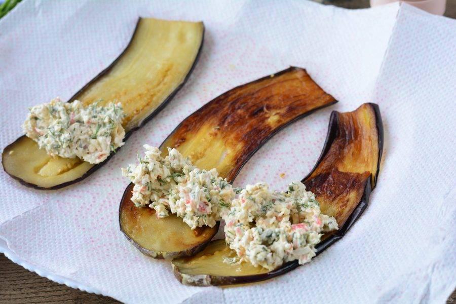 Жареные баклажаны выложите на салфетки, чтобы ушел лишний жир, на край выложите крабовую начинку.