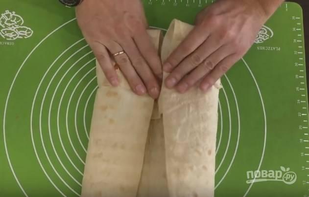 7. Заверните низ лаваша на начинку, потом сложите внутрь бока лаваша и аккуратно сверните в рулет. Если лаваш несвежий, то он может лопнуть.