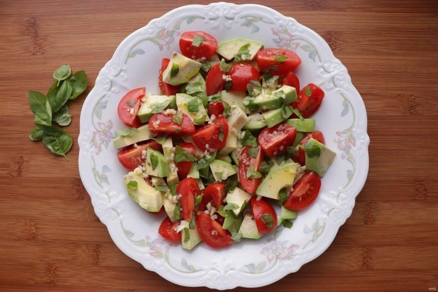На плоскую большую тарелку выложите авокадо, сверху распределите помидоры, нарвите руками листья базилика и полейте заправкой.