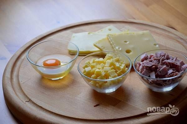 1.Одно яйцо вбиваю в миску, одно оставляю для смазывания. Сыр нарезаю кусочками, можно и на терку, ветчину нарезаю такими же кусочками, как и сыр.