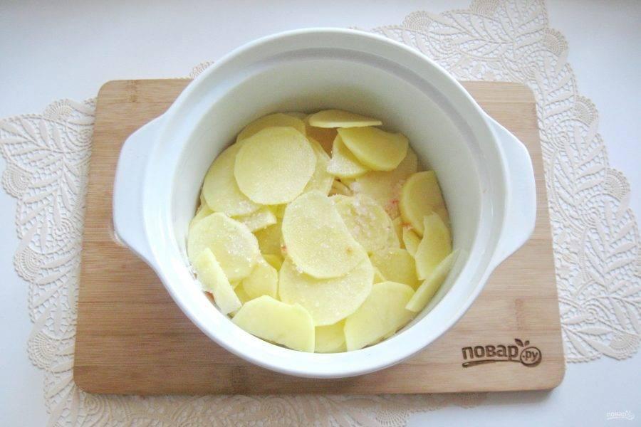 Картофель очистите, помойте и нарежьте пластинами толщиной 3-4 мм. Выложите в кастрюлю к луку и моркови. Немного посолите.