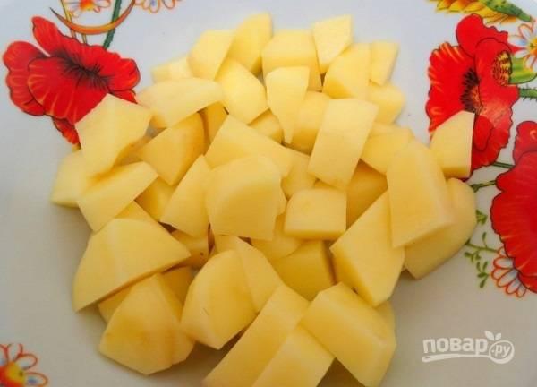 2. В кастрюлю налейте воду и поставьте на огонь. Тем временем очистите и нарежьте кубиками картофель.