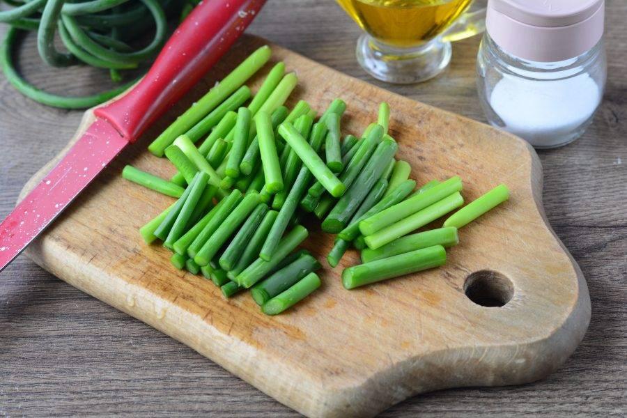 Чесночные стрелки промойте и нарежьте ножом на средние кусочки, чтобы они поместились в мясорубку.
