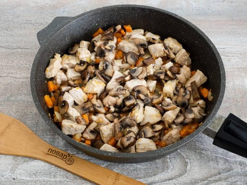 Когда морковь немного зажарится, добавьте нарезанное кусочками мясо. Жарьте всё вместе 15-20 минут помешивая, посолите по вкусу. Затем накройте крышкой и пожарьте под крышкой ещё 5-7 минут. Когда мясо будет готово выложите сверху жареные грибы.